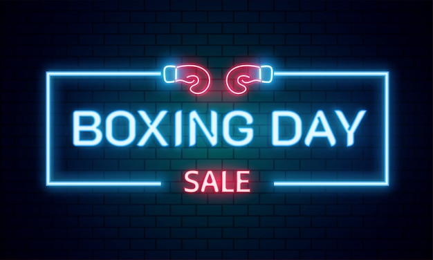 Neon text boxing day sale on brick wall background.