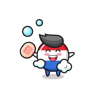 네덜란드 국기 배지 캐릭터가 비누, 티셔츠, 스티커, 로고 요소를 위한 귀여운 스타일 디자인을 들고 목욕하고 있습니다 프리미엄 벡터