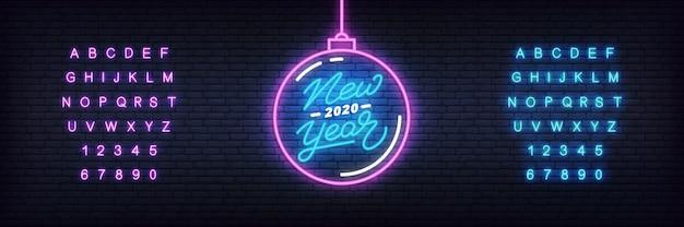 Новый год неон. светящийся неоновый елочный шар и надписи к празднованию нового 2020