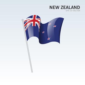 グレーに分離されたニュージーランドの旗を振っています。