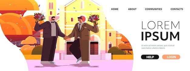 교회 트랜스젠더 사랑 lgbt 커뮤니티 결혼 축하 근처에 함께 서 있는 꽃을 든 신혼 게이 커플
