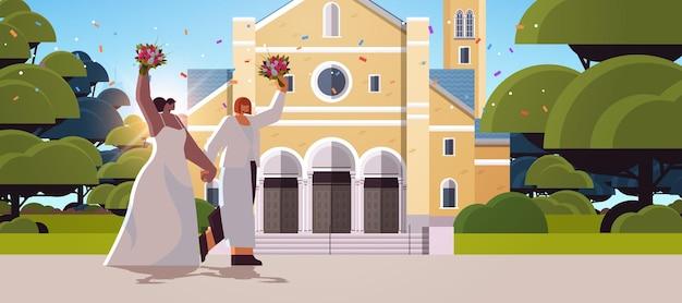 Newlywed lesbian couple with flowers standing near church transgender love lgbt community wedding celebration