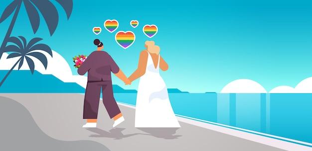 Молодожены лесбиянки с цветами гуляют по пляжу трансгендеры любят свадьбу лгбт-сообщества