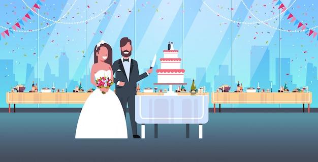 新婚夫婦ちょうど結婚した男性女性恋愛結婚式の日の概念のロマンチックなカップルの新郎新婦一緒に甘いケーキを切るモダンなレストランインテリア全長水平
