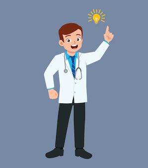 電球のサインで立っている素敵な格好良い若い医者