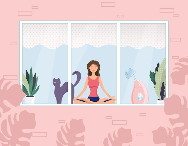A nice young woman is sitting in a yoga and meditation pose with a cat next to her. meditation, relaxation at home with a view from the window.