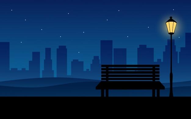 公共の公園でベンチと街の夜