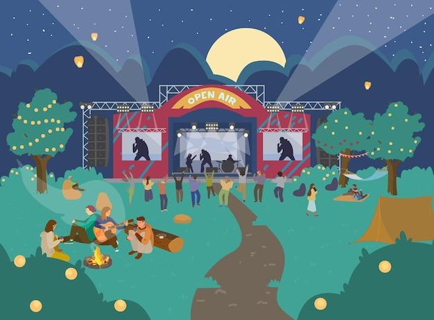 夜の音楽祭野外。音楽の舞台、人々が踊り、リラックスし、焚き火の近くに座っています。