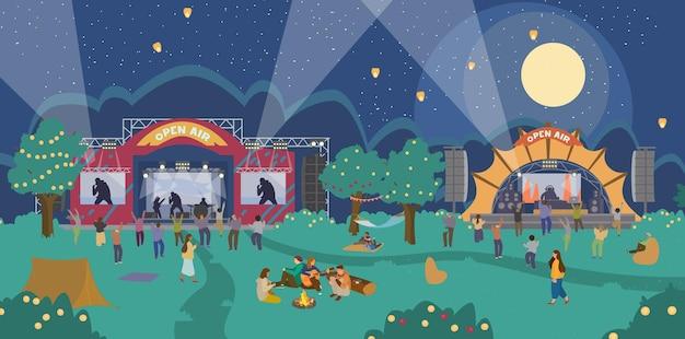 夜の音楽祭野外。音楽の舞台、踊る人々、リラックスする人々、焚き火の近くに座る人々。