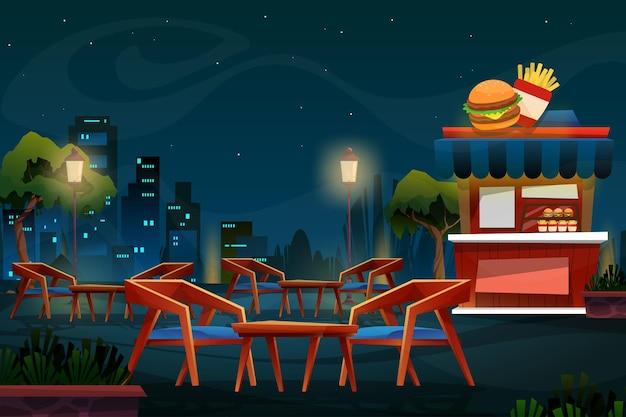 자연 공원에서 의자와 테이블이 있는 햄버거와 감자 튀김 가게의 야경
