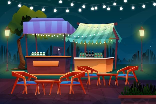 자연 공원 근처에 의자와 테이블이 있는 미니 부스 또는 음료 가게의 야경