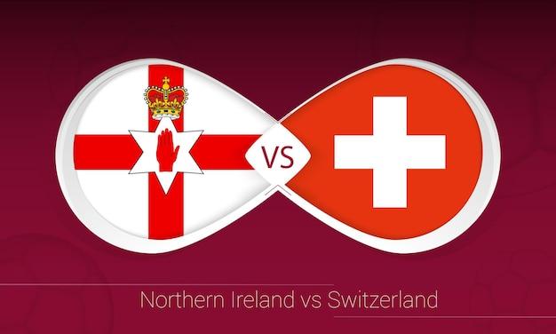 Северная ирландия против швейцарии в футбольном соревновании, группа c. против значка на футбольном фоне.