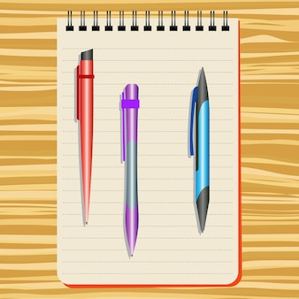 Notebook,  red  pen, purple pen and blue pen on a wooden table