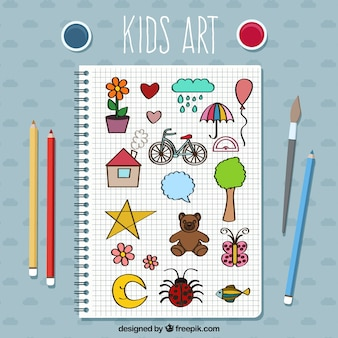 Notebook with kid drawings and pencils
