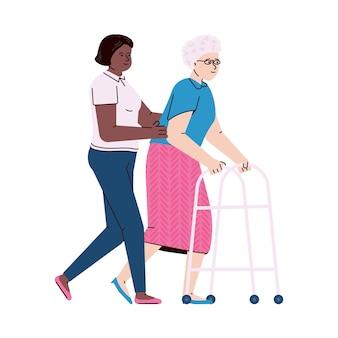 Медсестра помогает пожилой пациентке ходить с ходунками.