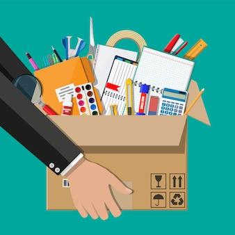 Офисные принадлежности в картонной коробке в руке.