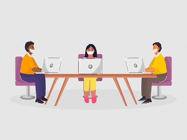 Офисные работники поддерживают социальную дистанцию при совместной работе на рабочем месте.
