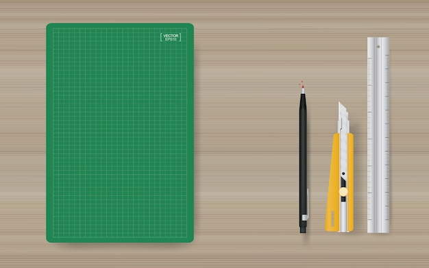 Office object background of green cutting mat with ruler, cutter and pencil on wood.