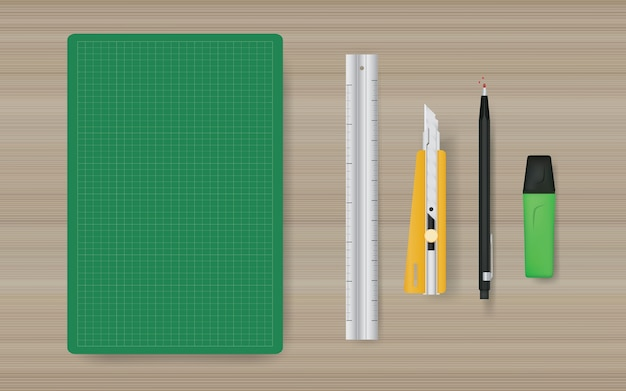 ルーラー、カッター、鉛筆、マーカーのある緑色のカッティングマットのオフィスオブジェクトの背景