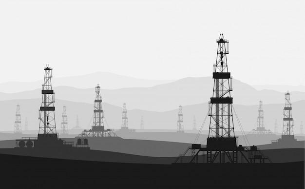 Нефтяные вышки на большом месторождении над горным хребтом.