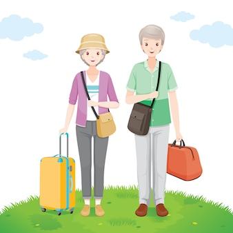 一緒に荷物を芝生の上に立っている古い男性と女性の旅行者