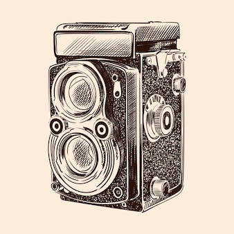 Old vintage camera with two lenses isolated on a beige background.