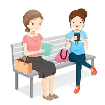 老婆読書本、スマートフォンを再生する若い女性。彼らは一緒にベンチに座っています。