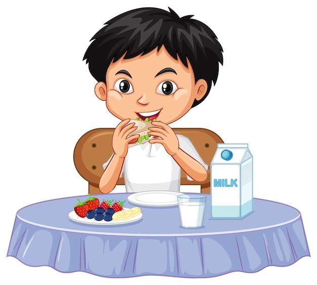 テーブルの上で食べる一人の幸せな少年