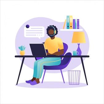 Целевая страница помощника онлайн. афро-американский человек с наушниками с компьютером. концепция иллюстрации для поддержки, помощи, колл-центр. виртуальная справочная служба. иллюстрация в квартире.