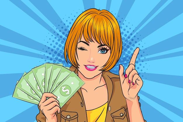 オンラインベッティング、インターネットでの収益。お金を指しているポジティブな女性、私たちにドル紙幣を見せてくれるフリーランサー、ラップトップのホームオフィスで職場に座っている
