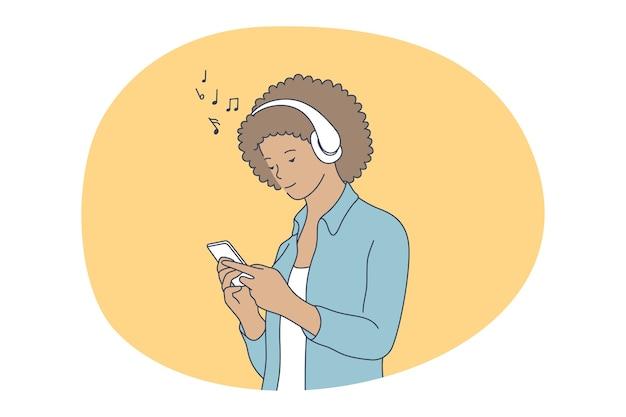 オンラインコミュニケーション、スマートフォンのコンセプトで音楽を聴く。ヘッドフォンで若い笑顔の女の子