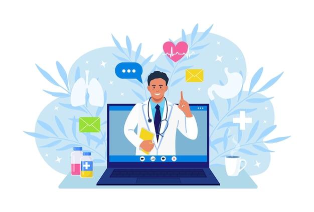 온라인 의사. 치료사에게 물어보세요. 온라인 의료 상담, 상담, 지원 서비스. 의사는 인터넷을 통해 진단을 수행합니다. 노트북 화면에 청진기가 있는 흰색 코트를 입은 남자