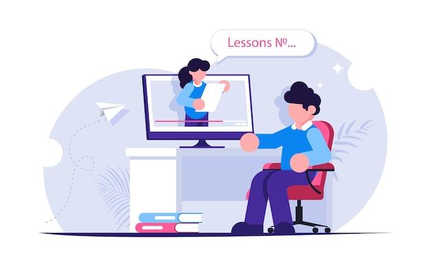 オンライン教育。レッスンやウェビナーのビデオを見ながら机に座っている人
