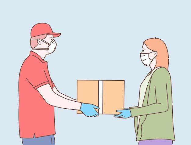 オンラインの安全な配達サービス。コロナウイルス検疫中に女性にパッケージまたはボックスを配信する医療マスクを持つ若い宅配便の男性