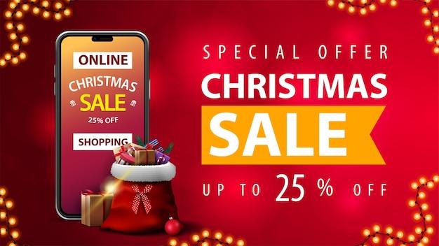 온라인 쇼핑, 특별 행사, 크리스마스 세일, 최대 25 % 할인, 배경이 흐린 빨간색 할인 웹 배너, 화면에 제공되는 스마트 폰 및 주변에 선물이있는 산타 클로스 가방