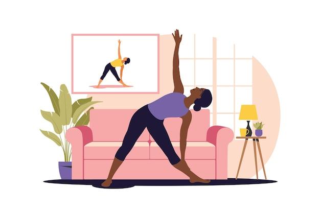オンライントレーニングの概念。家でヨガをしているアフリカの女性。テレビでチュートリアルを見ています。スポーツ運動