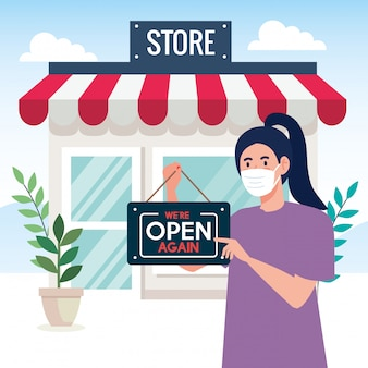 Open again after quarantine, woman with label of reopening of shop, we are open again, store shop facade