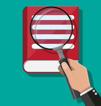 Open book and hand with magnifying glass