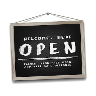 Open sign on black chalkboard in wooden frame. information sign for front the door about working again. keep social distance and wear face mask.  isolated on white.