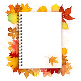 Open spiral notebook with autumn leaves