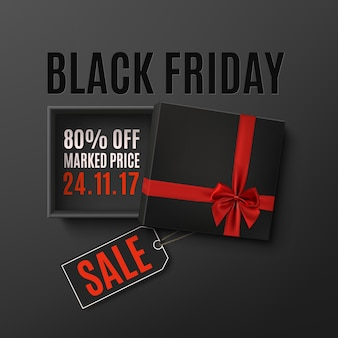 Opened black empty gift box with red ribbon, bow and price tag on dark background. top view.