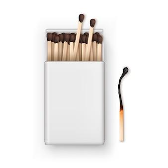 Открытая пустая коробка с коричневыми спичками с обожженной спичкой сверху на белом фоне