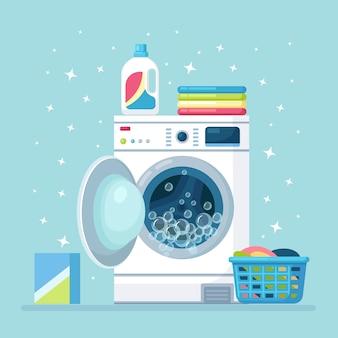 바구니에 마른 옷과 세제를 넣은 세탁기를 열었습니다. 전자 세탁 장비.