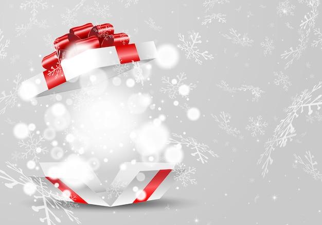 Открыт белая подарочная коробка с красным бантом и огнями на фоне снежинки
