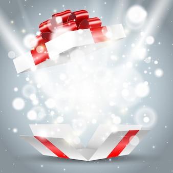 Открыт белая подарочная коробка с красным бантом и огнями