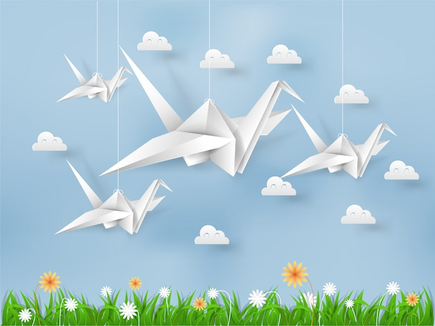 Origami birds flying on blue sky over field of grasses and flowers