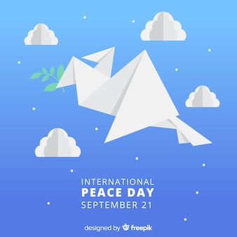 Origami dove holding branch surrounded  by clouds and stars