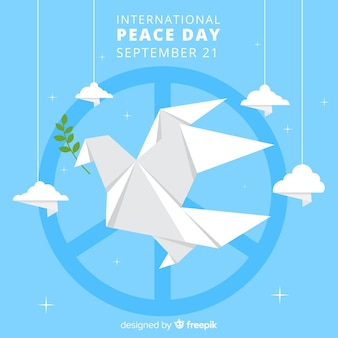 Origami dove with peace symbol and clouds around it