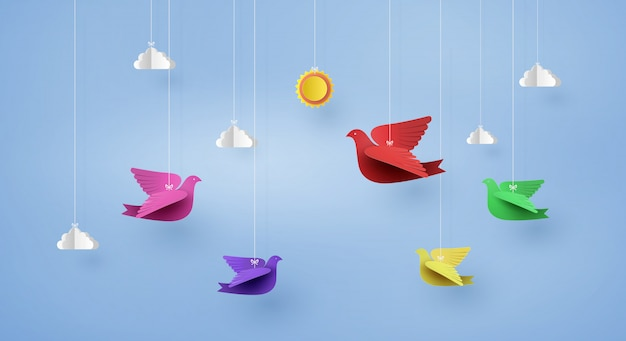 Origami made colorful paper bird flying on blue sky