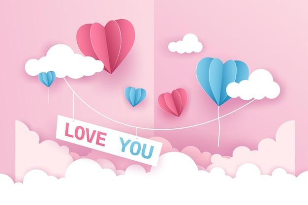雲の上空を飛んでいる折り紙の風船のハート型のピンクとブルーの色。
